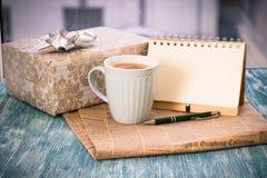 与箱子、杯子、笔记本和笔的镭欢乐静物画 图库摄影