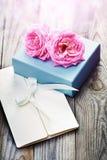 与箱子和信件的桃红色玫瑰在葡萄酒s的木背景 库存照片