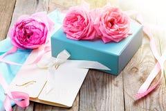 与箱子和信件的桃红色玫瑰在葡萄酒s的木背景 免版税图库摄影