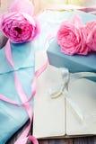 与箱子和信件的桃红色玫瑰在葡萄酒s的木背景 图库摄影