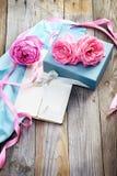 与箱子和信件的桃红色玫瑰在葡萄酒s的木背景 免版税库存照片