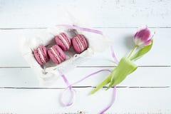 与箱子和郁金香的甜绯红色法国蛋白杏仁饼干在光洗染了木背景 免版税库存图片
