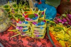 与箱子的一个市场由叶子制成,在花的安排里面在一张桌,在市登巴萨在印度尼西亚 库存照片