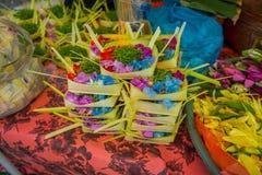 与箱子的一个市场由叶子制成,在花的安排里面在一张桌,在市登巴萨在印度尼西亚 库存图片