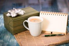 与箱子,杯子,报纸,有笔的笔记本的RFestive静物画 库存图片