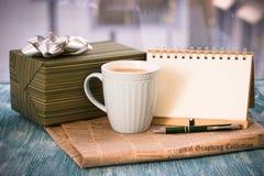 与箱子,杯子,报纸,有笔的笔记本的RFestive静物画 免版税库存图片