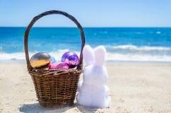 与篮子和颜色的复活节兔子在海洋海滩怂恿 免版税库存照片