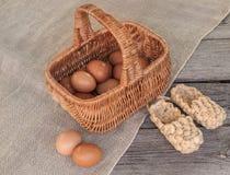 与篮子的土气静物画用鸡蛋和韧皮鞋子 免版税图库摄影