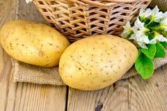 与篮子的土豆黄色在麻袋布 库存图片