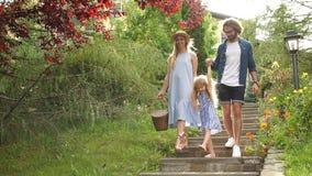 与篮子的年轻家庭在野餐以后步行沿着向下台阶的外面在绿色公园 股票视频