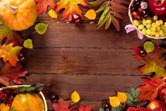 与篮子的秋天背景,黄色槭树离开,葡萄,红色苹果 秋天收获框架在年迈的木头的与拷贝空间 免版税库存图片