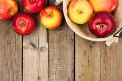 与篮子,在土气年迈的木头的顶面边界的苹果 免版税库存照片