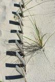 与篱芭和阴影的沙子 图库摄影