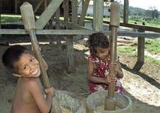 与米杵的印地安女孩和男孩打碎米 库存图片