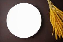 与米的耳朵的白色盘在棕色皮革背景的 库存图片