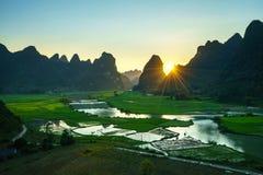 与米领域、河、山和低云的越南风景在清早在Trung Khanh,高平镇,越南 免版税库存图片