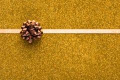 与米黄丝带的假日金黄背景 免版税图库摄影