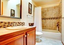 与米黄瓦片墙壁修剪的卫生间内部 图库摄影
