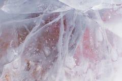 与粉红和橙色采摘的有裂痕的透亮冰纹理 免版税图库摄影