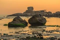 与粗砺的被堆积的岩石和冰砾的自然海景在日出的Hon Chong海角 免版税图库摄影