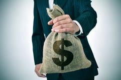 与粗麻布金钱袋子的商人 免版税库存图片