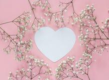 与精美矮小的白色flowe框架的白纸心脏卡片  免版税库存照片