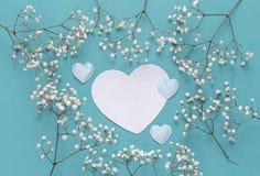 与精美矮小的白色flowe框架的白纸心脏卡片  免版税库存图片