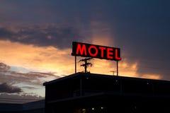 与精采日落的红色汽车旅馆标志 免版税库存图片