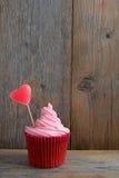 与糖果心脏的桃红色杯形蛋糕 库存照片