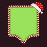 与糖果框架和圣诞老人帽子的绿色空的横幅 免版税图库摄影