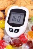 与糖水平和糖果的坏结果的Glucometer用曲奇饼,减少吃甜点概念 免版税库存照片
