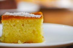 与糖浆revani的可口土耳其酥皮点心在一块白色板材 库存照片