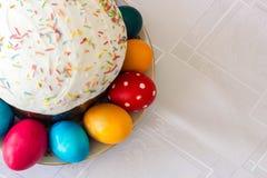 与糖渍的结冰和复活节彩蛋的复活节蛋糕在白色桌布背景 库存图片