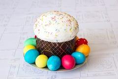 与糖渍的结冰和复活节彩蛋的复活节蛋糕在白色桌布背景 库存照片