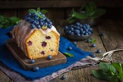与糖结冰和新鲜的莓果的蓝莓蛋糕 免版税图库摄影
