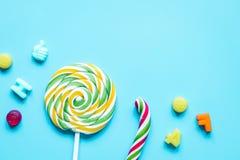 与糖candys的棒棒糖设计在蓝色背景顶视图mo 免版税库存照片