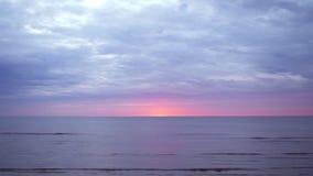 与紫罗兰色和洋红色颜色的令人惊讶的黑暗的风景生动的绯红色罕见的红色日落在有小太阳的波罗的海在 影视素材