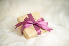 与紫色丝带的圣诞节礼物在温暖的白色毯子 库存照片