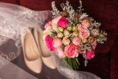与紫色和桃红色玫瑰的婚礼花束在焦点米黄鞋子盖了在背景的面纱 婚礼辅助部件在a说谎 免版税库存照片