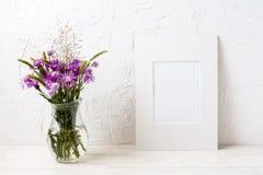与紫色植物名的白色框架大模型在玻璃水罐 图库摄影