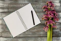 与紫色花、一个笔记本和一支铅笔的春天平的位置在一张灰色木桌上 免版税库存照片