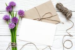与紫色野花花束的空白的白色与一条绳索的贺卡和信封在白色木桌 免版税库存照片