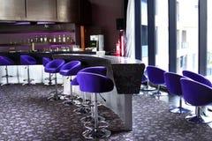 与紫色高凳和大窗口的酒吧 酒吧柜台 装瓶架子 图库摄影