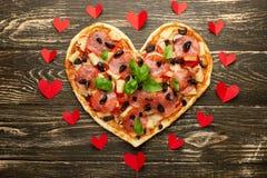 与红心的心脏比萨爱概念情人节浪漫晚餐意大利酥皮点心 在一张木表 平位置 图库摄影