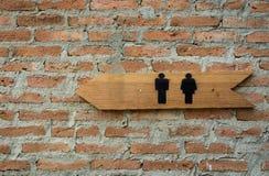 与红砖墙壁的洗手间标志 免版税库存图片