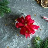 与红色丝带、金黄星、冷杉和糖果的圣诞节礼物在灰色背景的雪花 免版税库存照片