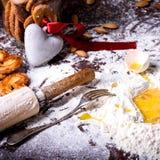 与红色丝带和成份的心脏标志在桌上的自创曲奇饼的 免版税图库摄影