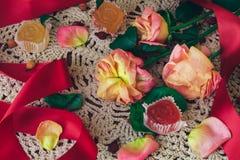 与红色丝带和橘子果酱的软绵绵的玫瑰在葡萄酒样式的一块白色鞋带小垫布 库存照片