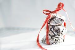 与红色丝带在一张白色烘烤的纸,关闭的美味的巧克力皱纹饼干,宏观 免版税库存图片