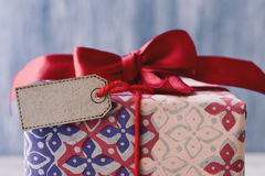 与红色丝带弓和空白的标签的礼物 图库摄影